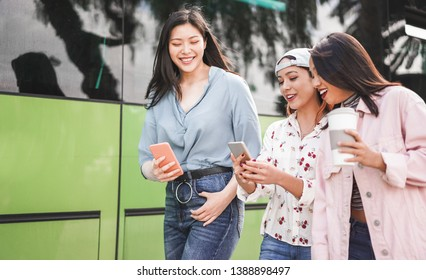 Happy asian friends using smartphones at bus station - Young students people having fun with technology trends after school - Friendship and transports app concept - Focus on center girl face