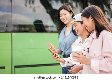 Happy asian friends using smartphones at bus station - Young students people having fun with phones app after school - Friendship, university and trasports concept - Focus on center girl phone  hand
