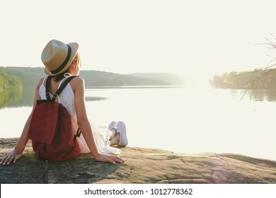Happy Asian girl backpack in nature enjoying on the stone patio in front of lake , Relax time on holiday concept travel,selective and soft focus,tone of hipster style.