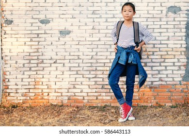 Happy Asian girl backpack  in old wall background, Relax time on holiday concept travel ,color of vintage tone and soft focus