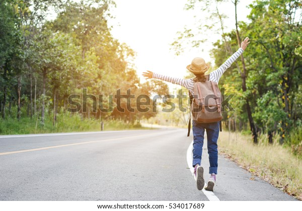 Happy Asian girl backpack  in the road and forest background, Relax time on holiday concept travel ,color of vintage tone and soft focus