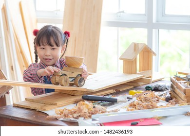 Happy asian girl carpenter craft a car out of wood and play on woodworking table.  Family, carpentry, woodwork and people concept.