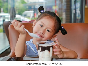 Happy asian girl eating ice-cream in the cafe with looking straight.