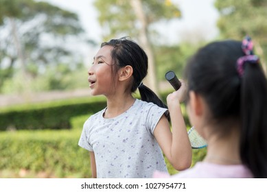 Happy Asian girl holding badminton and talking with friend.