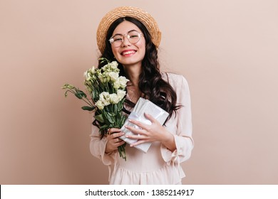 Happy asian girl holding present and flowers. Smiling chinese woman in hat posing with eustoma bouquet.