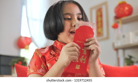 Happy Asian girl holding red pocket envelope from Chinese New year Celebration