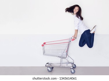 happy asian girl jump up shopping cart on white background. Potrait asian woman smile shoaholic with blank trolley for product display or sale festival concept.