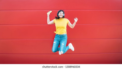 Happy Asian girl jumping while listening music outdoor - Crazy Chinese woman having fun dancing a song against red background - People entertainment with millennial generation and technology concept