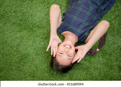 Happy Asian girl laying down on the green grass with copy space