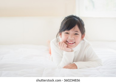Happy asian girl lying on the bed