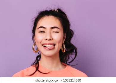 Happy asian girl making funny faces. Front view of trendy japanese young woman in earrings.