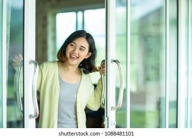 Happy asian girl open the glass door