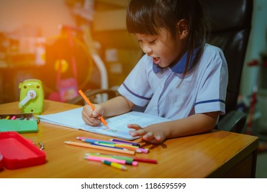 Happy Asian girl painting picture homework in book on wooden table at home by crayon