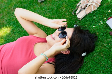 Happy asian girl at the park lying on the grass with sunglasses