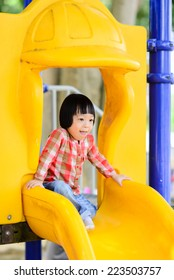 Happy Asian girl playing at playground.