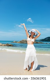 Happy, asian girl posing with arm raised on the tropical beach.Copy space