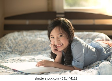 Happy asian girl reading a book on the bed,education concept