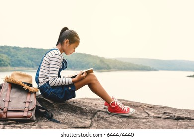 Happy Asian girl reading a book in nature background, Relax time on holiday, color of vintage tone and soft focus