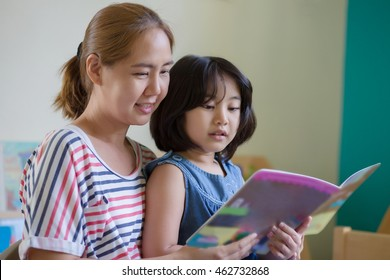 Happy Asian girl reading story book with her mother together