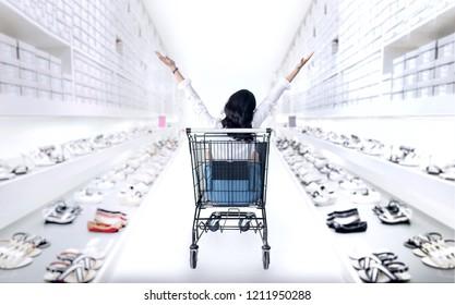 happy asian girl in shopping cart enjoy to shoping fashion shoes shop