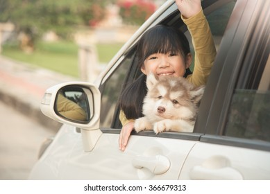 Happy asian asian girl and siberian husky puppy sitting in the car
