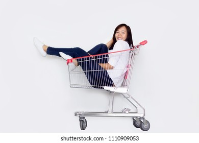 happy asian girl sitting in shopping cart on white background. Shopping action model.