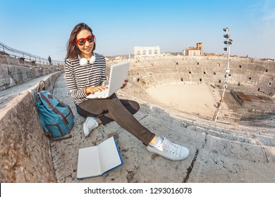 Happy asian girl student doing her homework with notebook pc or freelance working, while sitting in the european landmark amphitheater. Vacation and studying concept