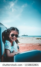 Happy asian girl in sunglasses smiling with perfect smile at beach while sitting in car. Outdoor on summer day. Travel on vacation concept. Teal and orange filter