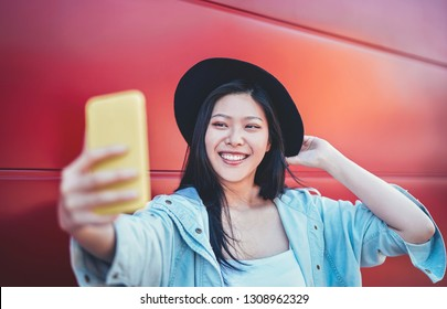Happy Asian girl taking selfie video story with mobile smart phone outdoor - Chinese trendy woman having fun with new trends social networks app - People, millennial generation and technology concept