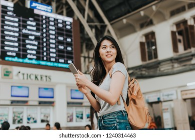 Happy Asian girl traveller use smartphone front of ticket booth at train station