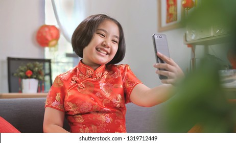 Happy Asian girl use smartphone for make video call with her family, Chinese New Year Celebrations