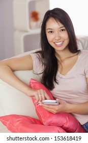 Happy asian girl using her smartphone on the couch looking at camera at home in the living room