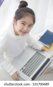 Happy Asian girl using laptop on the bed