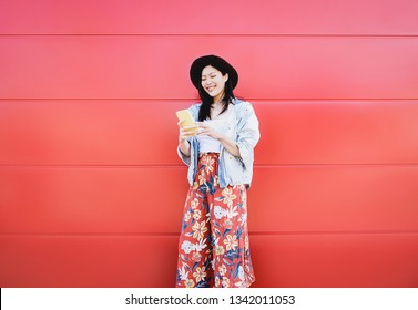 Happy Asian girl using mobile phone outdoor - Chinese social influencer having fun with new trends smartphone apps - Generation z, media, technology and youth millennial people lifestyle