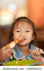Happy Asian girl in a vintage shirt eating pizza at home. Adorable little child girl enjoy eating pizza in summertime. Cute baby eating pizza in the restaurant.