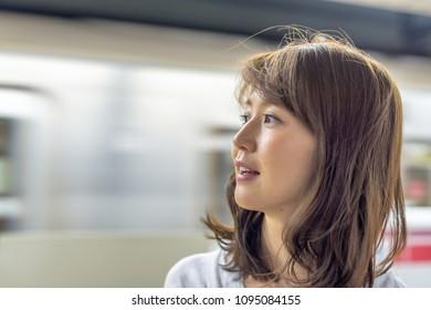 Happy asian girl waiting subway train.