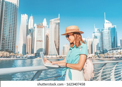 Happy asian girl works at a laptop in Dubai Marina port against the backdrop of high skyscrapers and the Bay