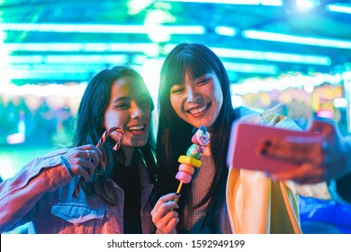 Happy asian girls eating candy sweets and taking selfie at amusement park - Young trendy friends having fun with technology trend - Tech, friendship and influencer concept - Focus on right female face