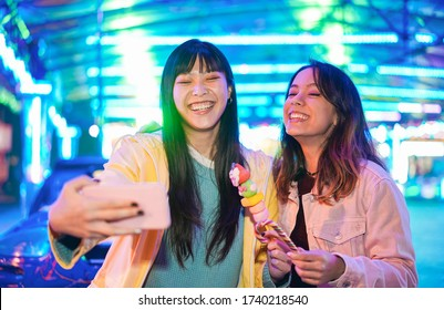 Happy asian girls eating candy sweets and taking selfie at amusement park - Young trendy friends having fun with technology trend - Tech, friendship and influencer concept - Focus on left female face