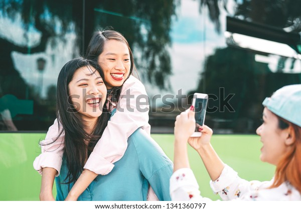 Happy Asian girls having fun outdoor - Millennial young people sharing time together and using mobile smartphone new trendy apps - Concept of friendship lifestyle with technology
