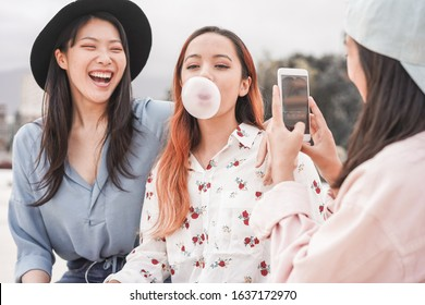 Happy asian girls making video story for social network app outdoor - Young women friends having fun making live feed - New technology trends and friendship concept - Focus on person blowing