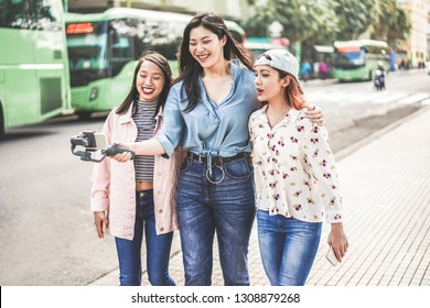 Happy asian girls making vlog video at bus station - Trendy friends blogging for social media outdoor - Technology lifestyle trends, city, casual clothes and friendship concept - Focus on right faces