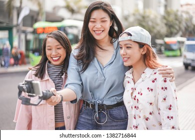 Happy asian girls making vlog video at bus station - Trendy friends blogging for social media outdoor - Technology lifestyle trends, city, casual clothes and friendship concept