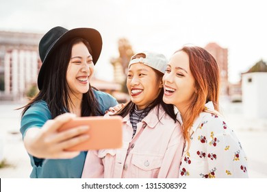 Happy Asian girls taking selfie with mobile smartphone outdoor - Young trendy teenager having fun with new technology app - People, social, friendship, tech and youth lifestyle concept