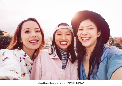 Happy Asian girls taking selfie with mobile smartphone outdoor - Young social friends having fun taking self photos outside - People, millennial generation and youth lifestyle concept