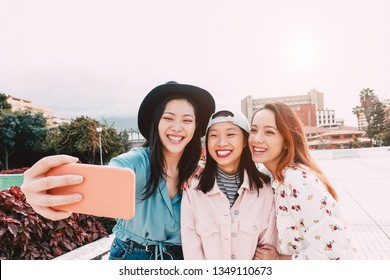 Happy Asian girls taking selfie with mobile smartphone outdoor - Young trendy teenager having fun with new technology app - People, social, media, friendship, tech and youth lifestyle people concept