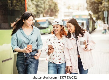 Happy Asian girls using mobile phone outdoor - Young millennial people having fun with new smartphone app technology - Concept of friendship, social, tech and teenager lifestyle