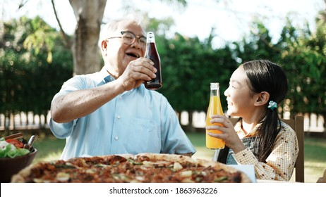 Happy asian grandchild drinking juice grandpa. Multi generation family enjoying meal. They having outdoor party eating food at backyard home, lifestyle family concept party at summer garden.