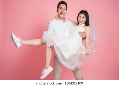 Happy Asian groom carrying his bride in casual wedding dress on pick background.