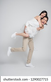 Happy Asian groom gives a bride piggyback ride on white background.
